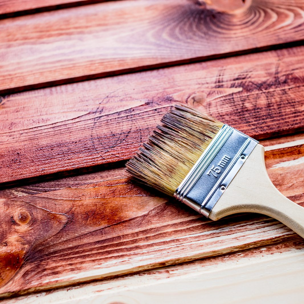 Varnishing a wooden shelf using paintbrush.brush and paint, stain, wooden floor, wall, repair, restoration concept.Paint brush on wooden table use for home decorated. House renovation. Copy space
