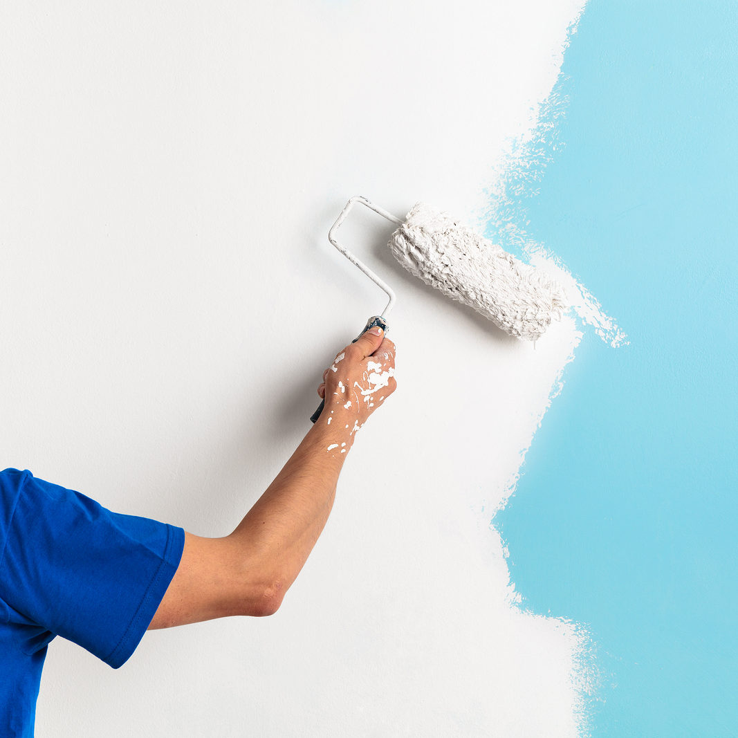 Back view of painter painting a wall with paint roller with copy space