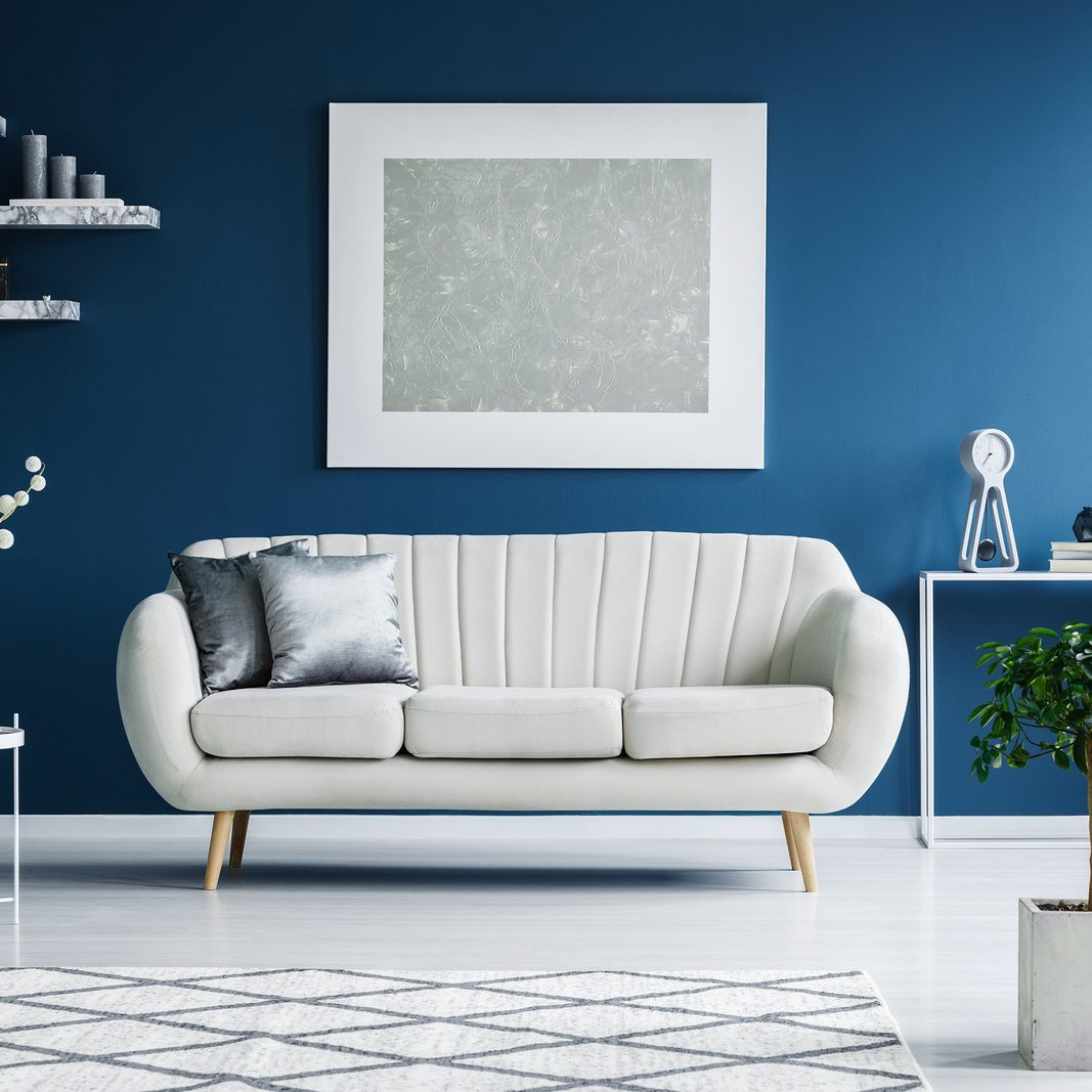 Leather sofa, floral paintings on the blue wall and flower in a vase in a living room interior